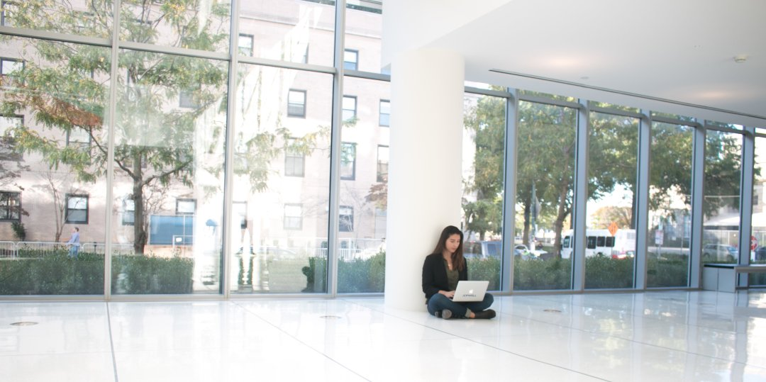 a student sits alone on the floor with a laptop in her lap, in front of a wall composed of glass mirrors.