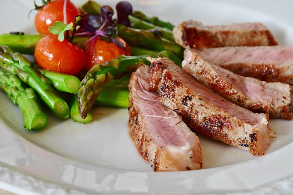 on a white plate, cherry tomatoes and asparagus are delicately placed next to a medium-rare veal chop, sliced thin and fanned